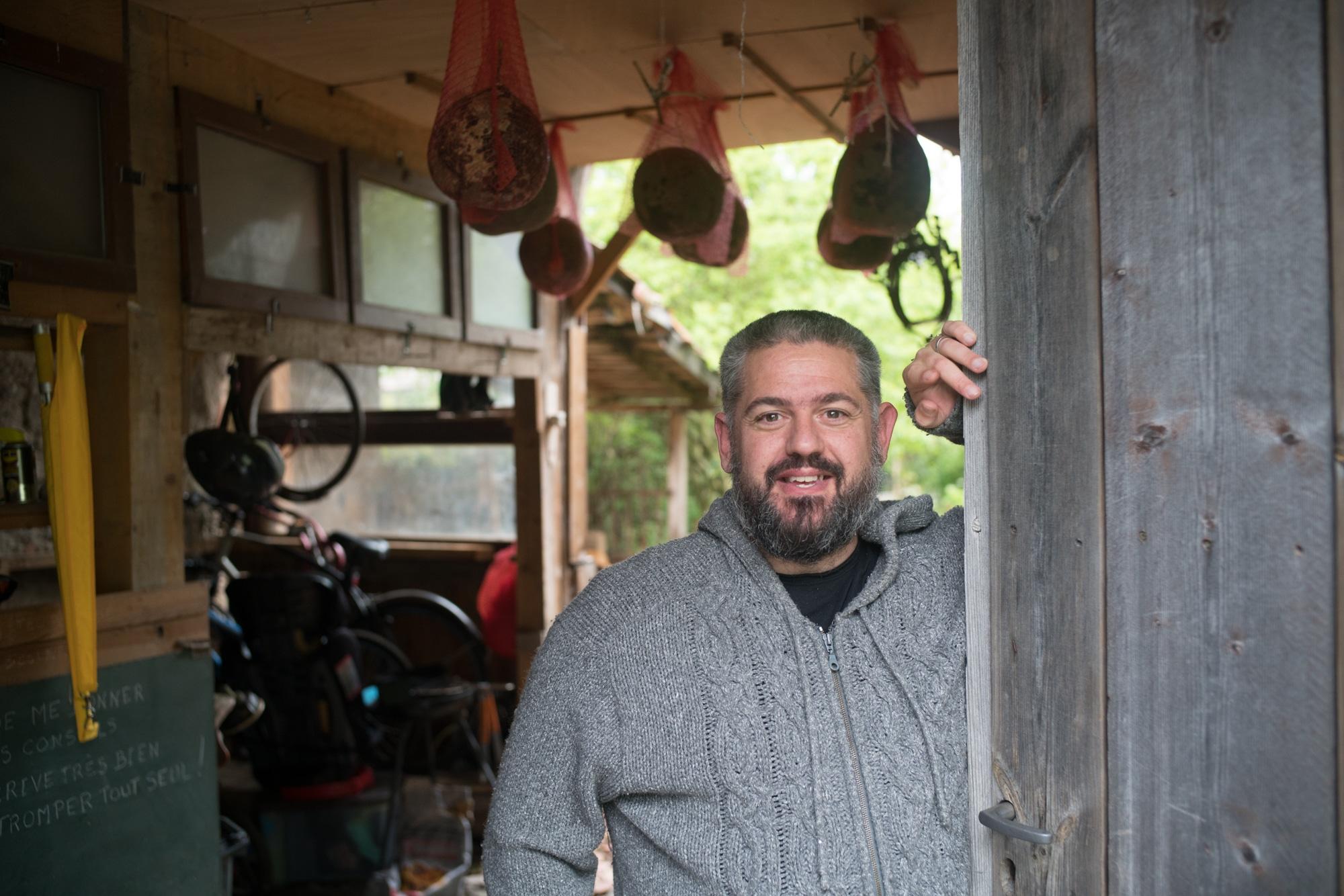 Laurent est adossé à une grande porte en bois devant son atelier