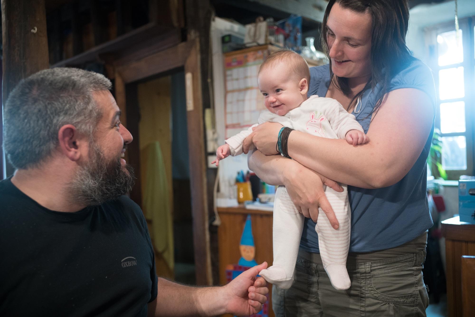 Laurent partage un sourire avec son fils qui est porté par sa femme