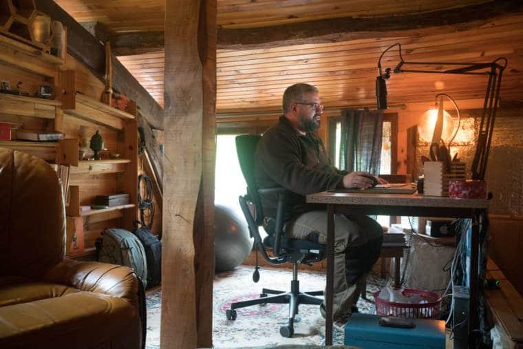 Laurent est de profil, assis à son bureau dans un environnement boisé