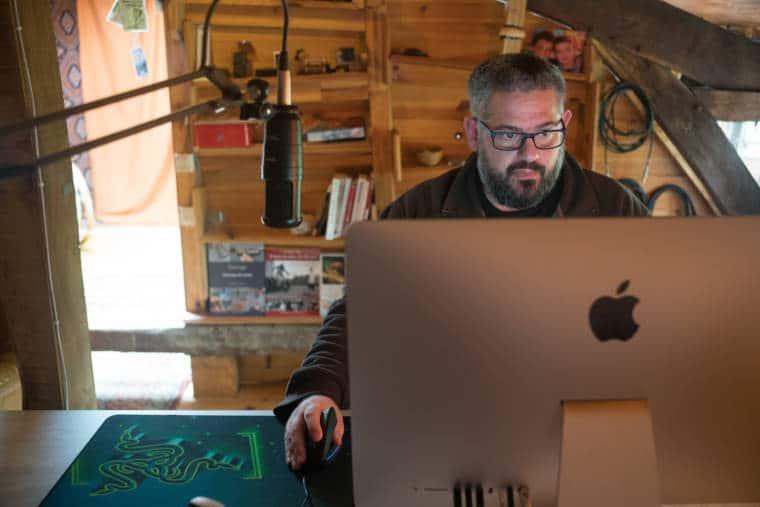 Laurent est assis derrière son ordinateur, derrière un micro