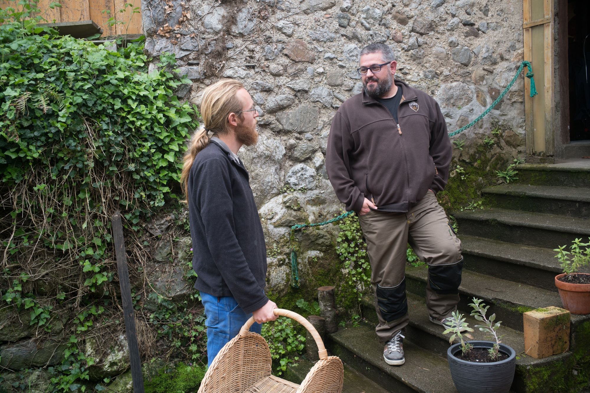 Postés sur des marches en extérieur, Laurent et un homme tenant un panier en osier discutent