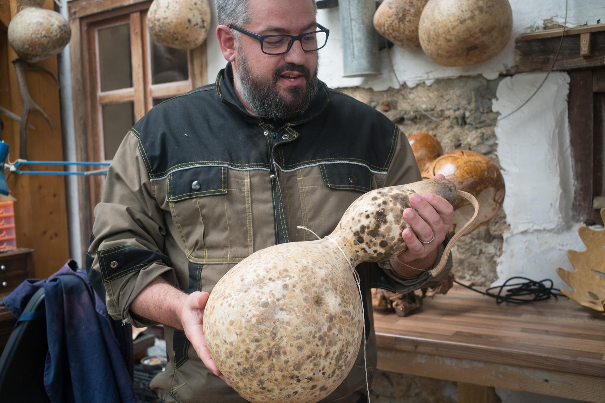 Laurent tient à deux mains une calebasse dans son atelier