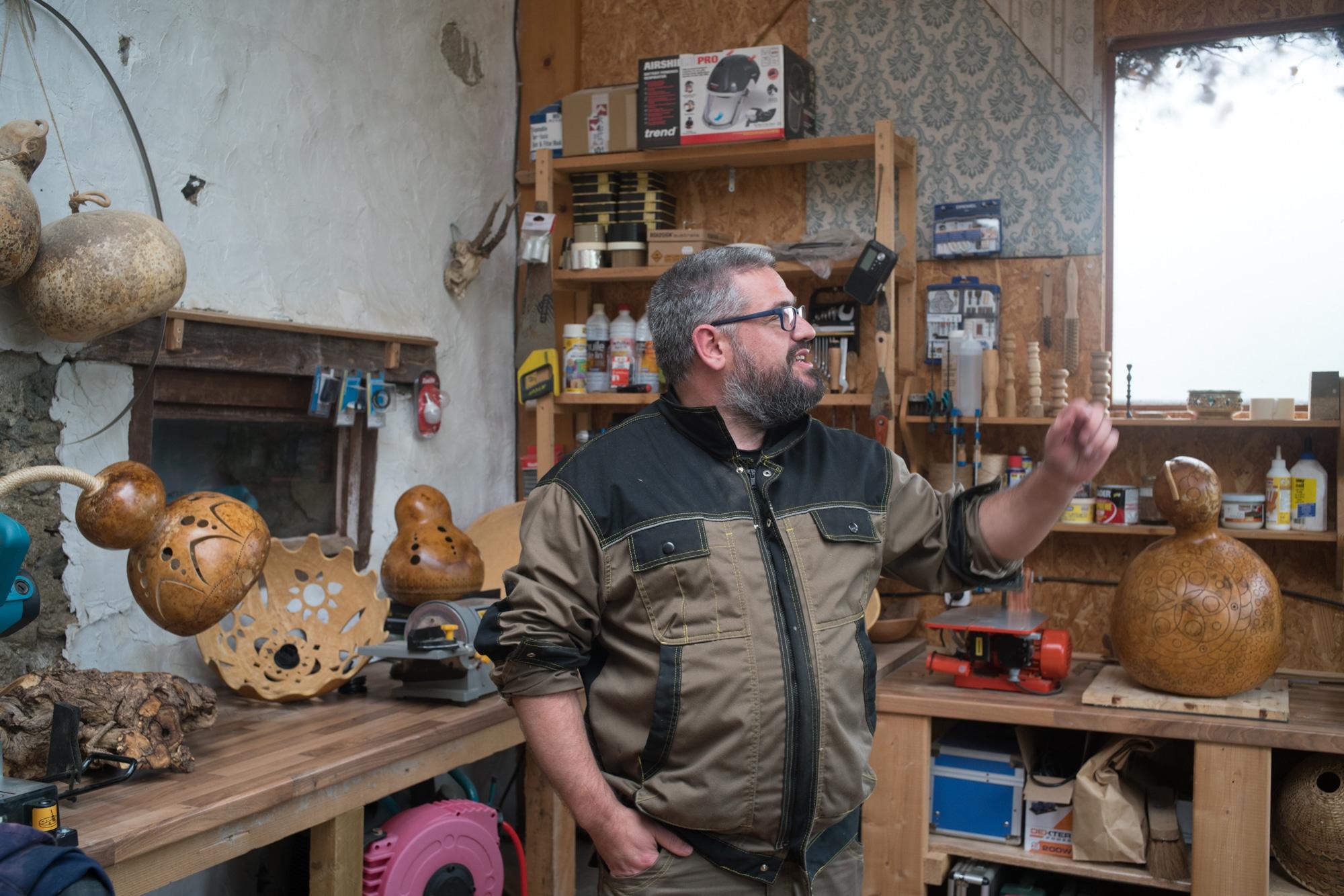 Laurent, dans son atelier, entouré de calebasses