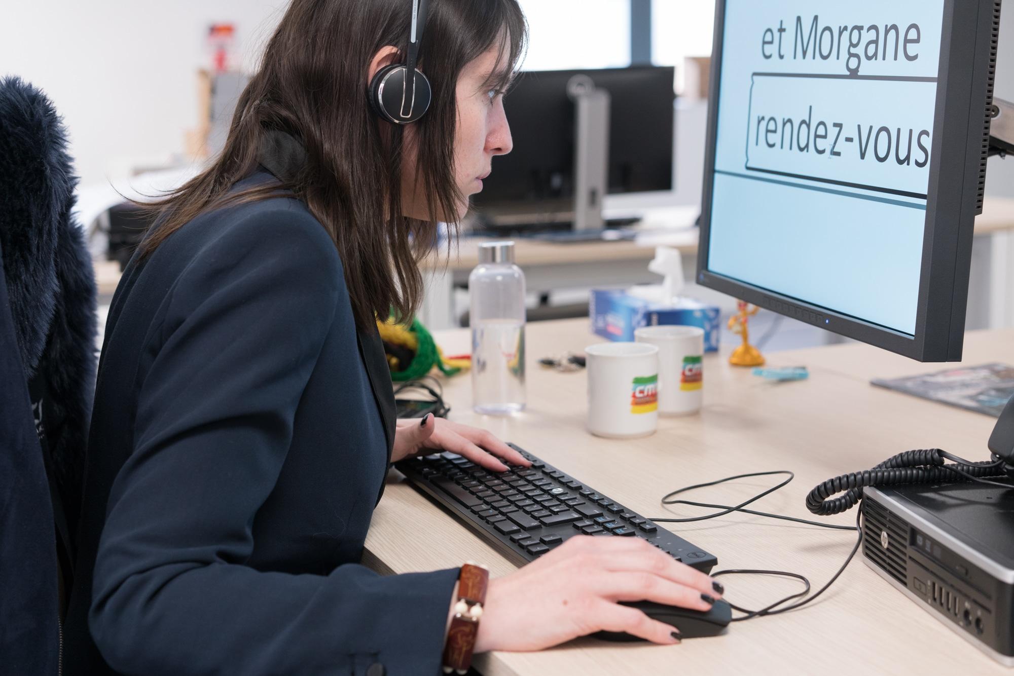 Morgane, équipée d'un casque audio, utilise son ordinateur.