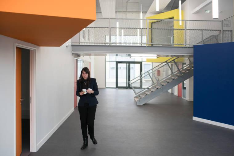 Un café à la main, Morgane marche dans les locaux de Chartres Métropole innovations numériques.
