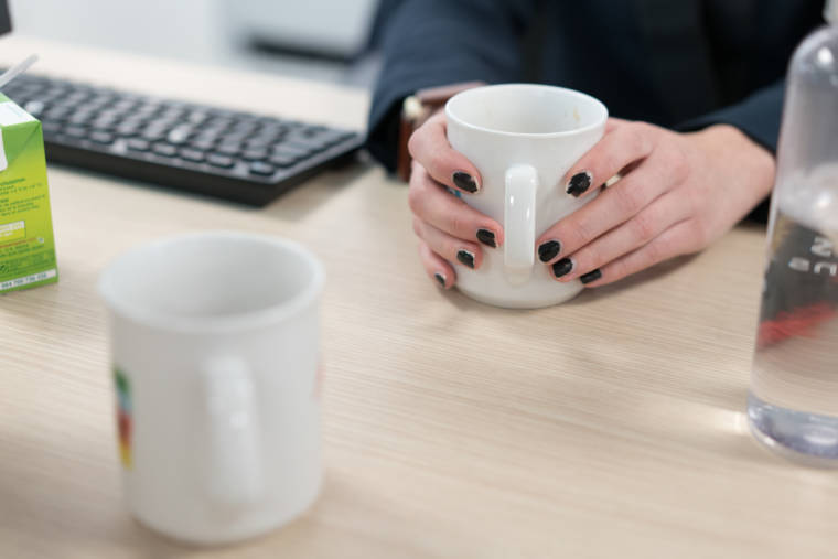 Les mains de Morgane serrent une tasse à café près d'un clavier d'ordinateur.