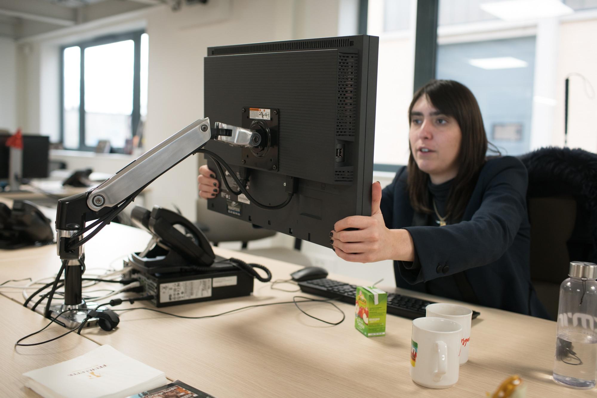 Morgane ajuste son moniteur d'ordinateur, fixé sur un bras mobile.