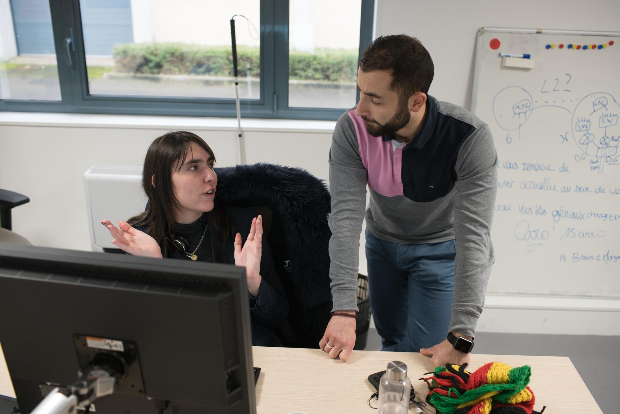 Morgane et un collaborateur discute devant l'ordinateur. Derrière eux on aperçoit un tableau sur lequel sont dessinés des schémas.