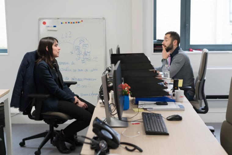 Morgane et un collaborateur discutent de part et d'autre d'un bureau.
