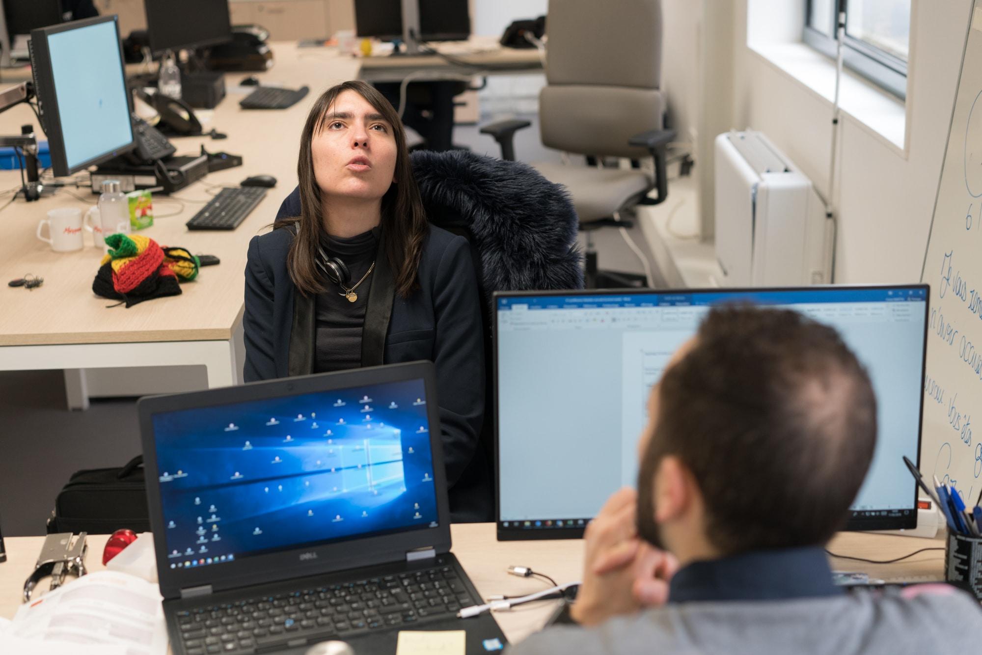 Morgane, assise devant le bureau de son collaborateur, discute avec lui, la tête penchée en arrière.