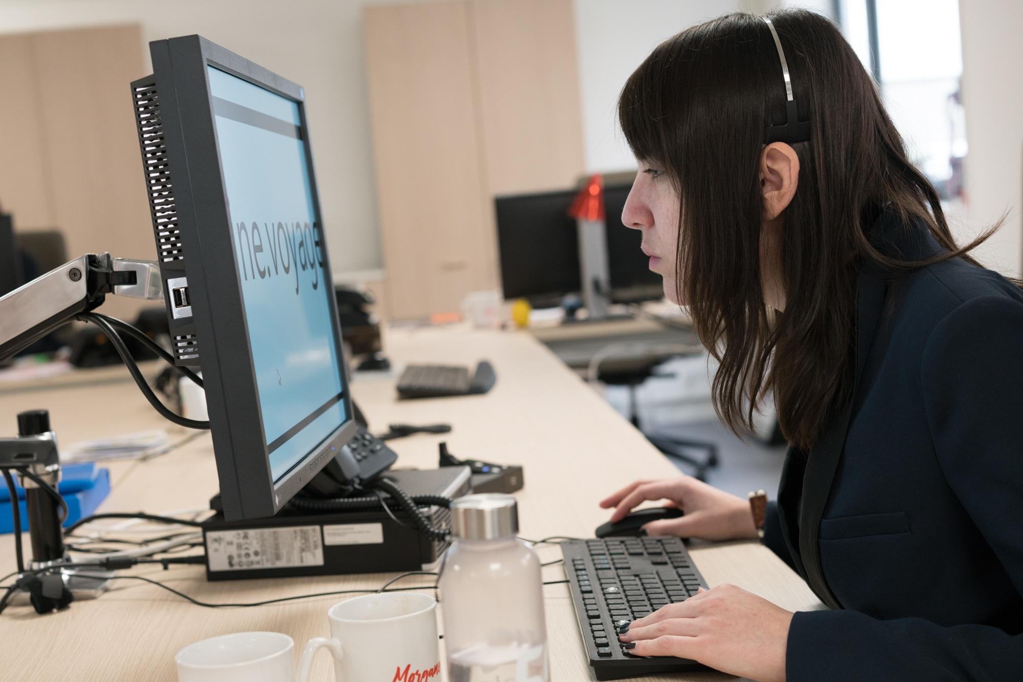 Morgane, de profil, utilise son ordinateur. On peut voir un mot s'afficher en gros à l'écran.