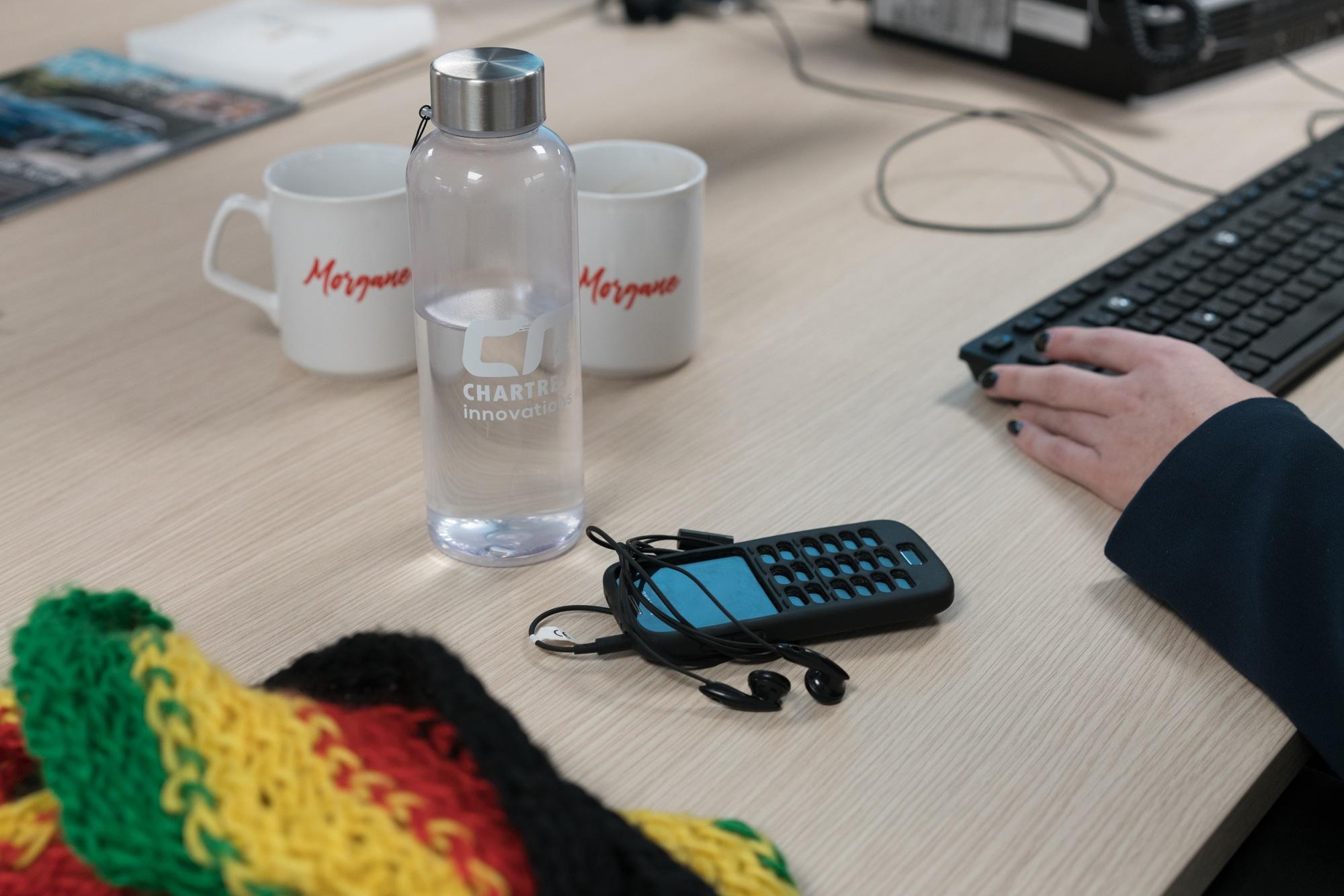 Sur le bureau de Morgane, on aperçoit des tasses, une bouteilles Chartres Innovations et un téléphone muni d'écouteurs.