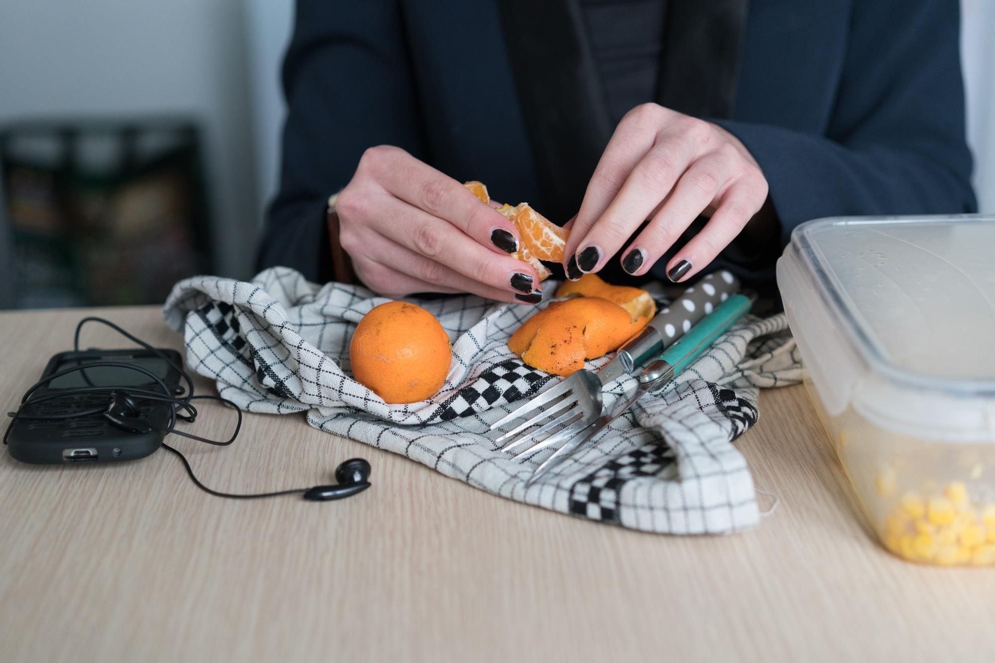 Les mains de Morgane, avec des ongles vernis en noir, épluchent une mandarine.
