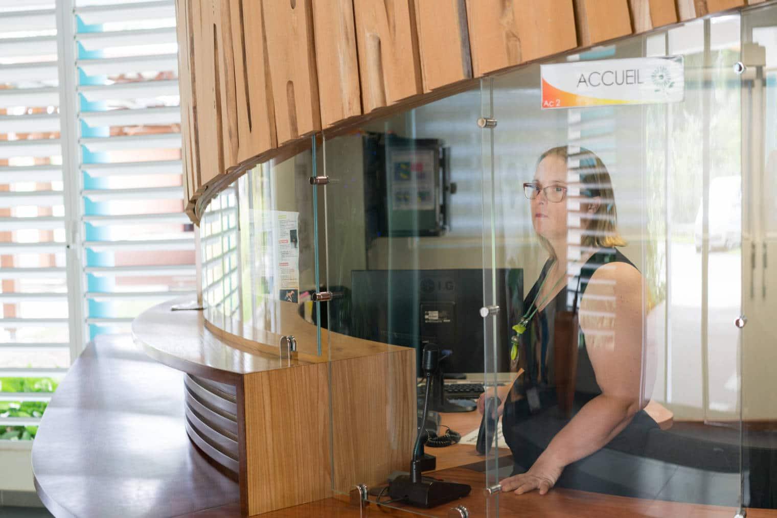 Lucy se tient debout dans son bureau d'accueil, derrière une vitre.