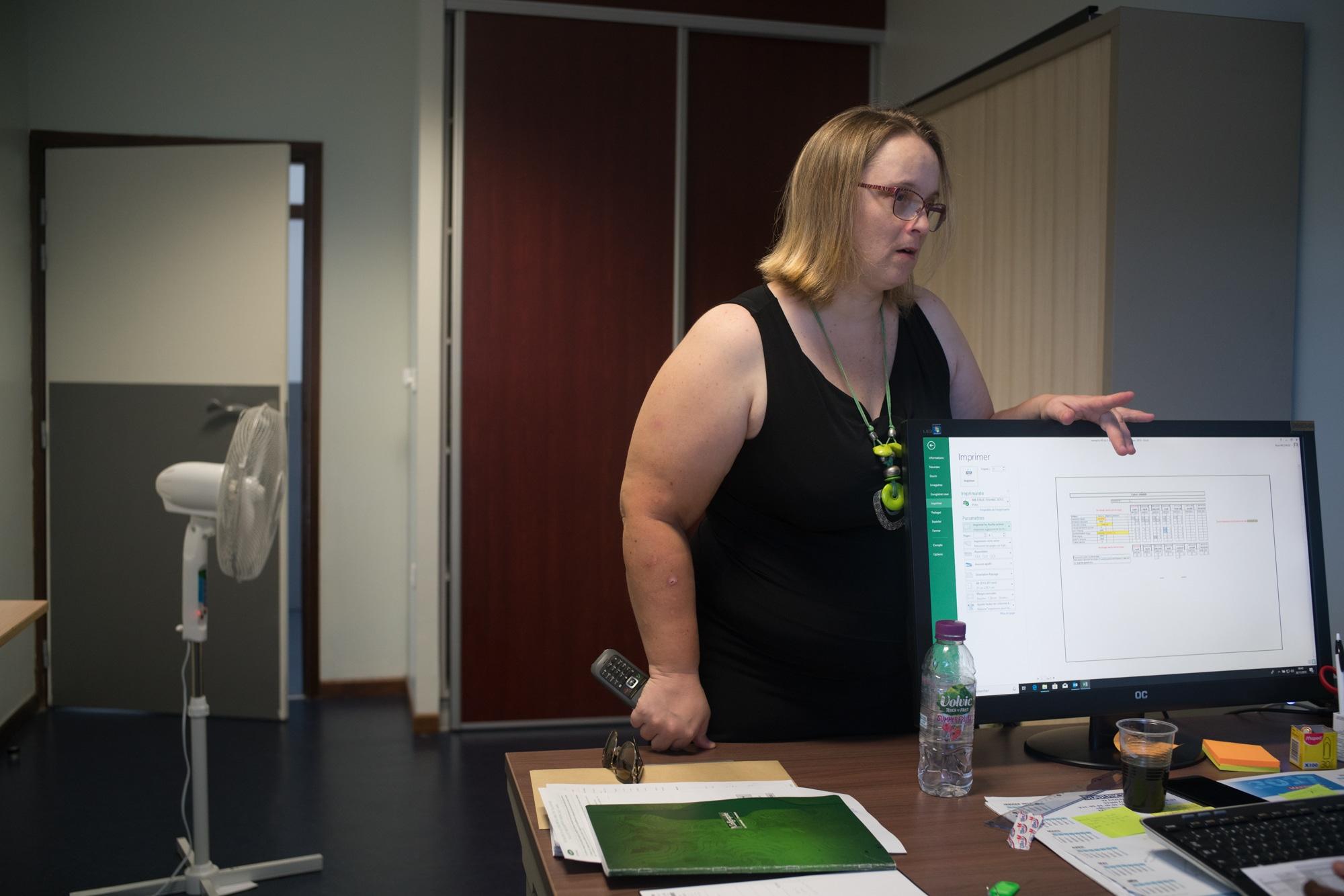 Une main sur le moniteur et l'autre sur le bureau, tenant un téléphone, Lucy s'adresse à un collaborateur.