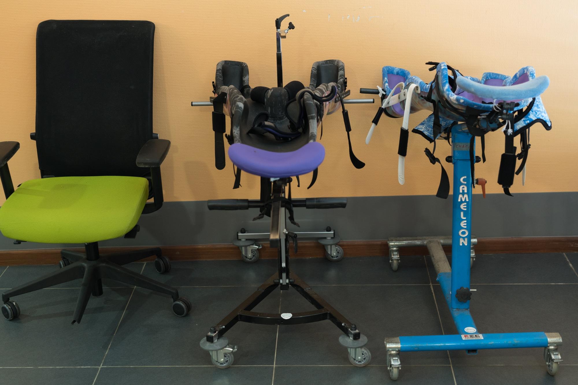Une chaise est placée à côté de deux chaises de transport pour enfants.