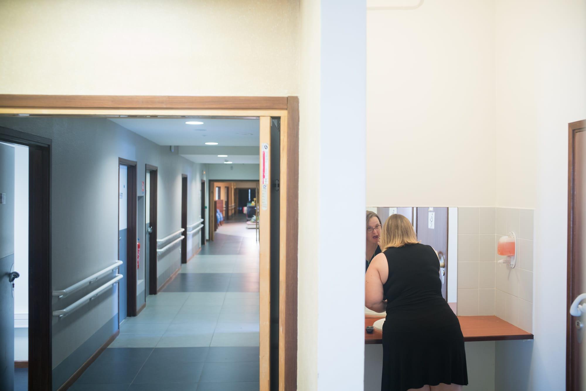 Séparée d'un couloir par une cloison, Lucy utilise un baume à lèvre devant un miroir.