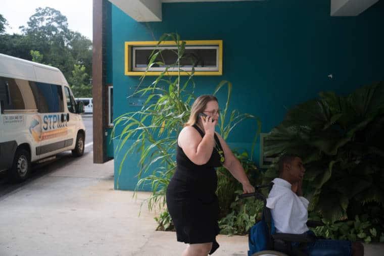 À l'extérieur du bâtiment, Lucy pousse un enfant sur un fauteuil roulant tout en téléphonant.