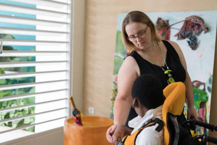 Penchée vers lui, Lucy caresse la main d'un enfant en fauteuil.