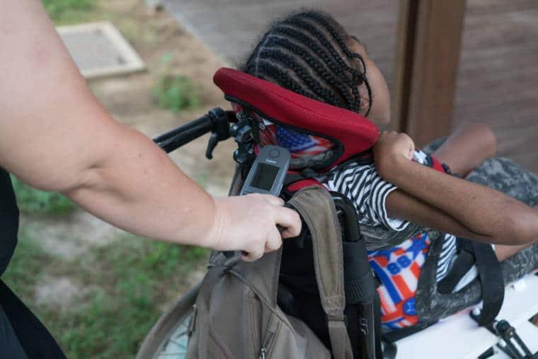 La main de Lucy, tenant le téléphone, pousse le fauteuil d'une enfant handicapée.