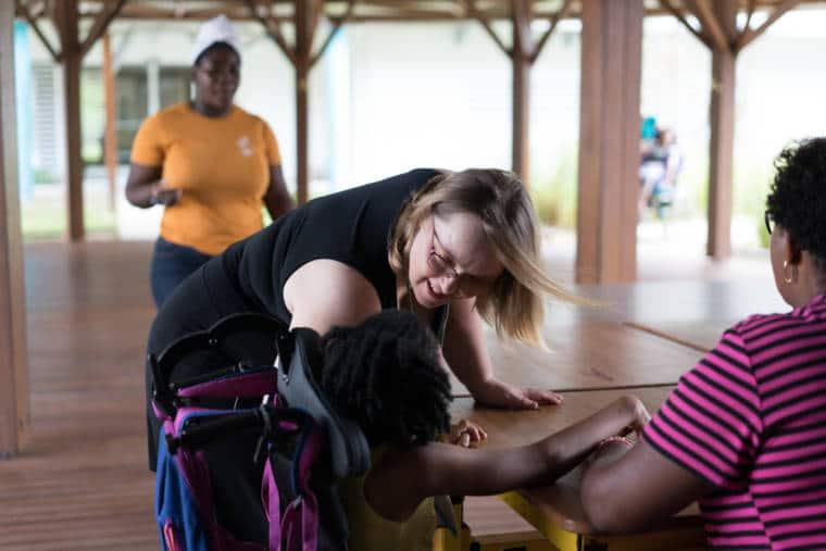 En extérieur, appuyée sur une table en bois, Lucy se penche en souriant vers une enfant handicapée.