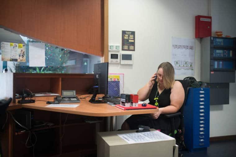 Assise à son bureau derrière son ordinateur, Lucy téléphone.