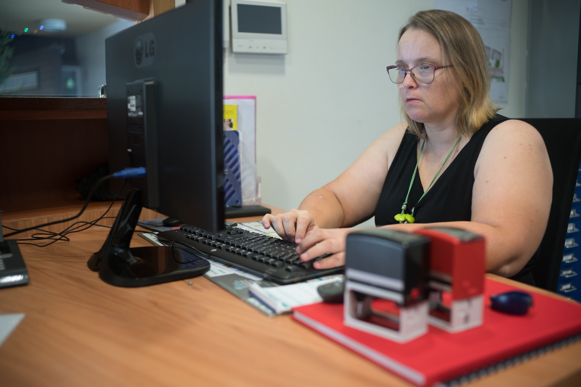 Assise à son bureau, Lucy consulte son ordinateur.