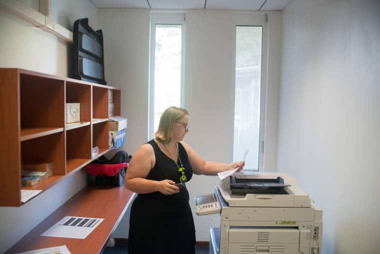 Lucy, un téléphone à la main, consulte un document devant une photocopieuse.