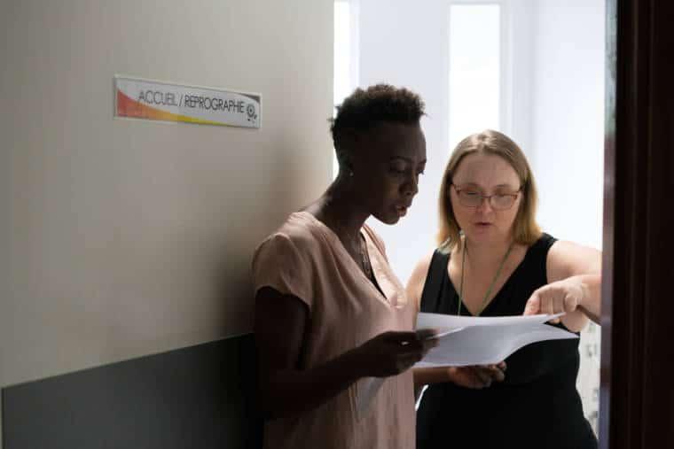 Lucy pointe une information sur un document à une collègue devant la porte de la reprographie.