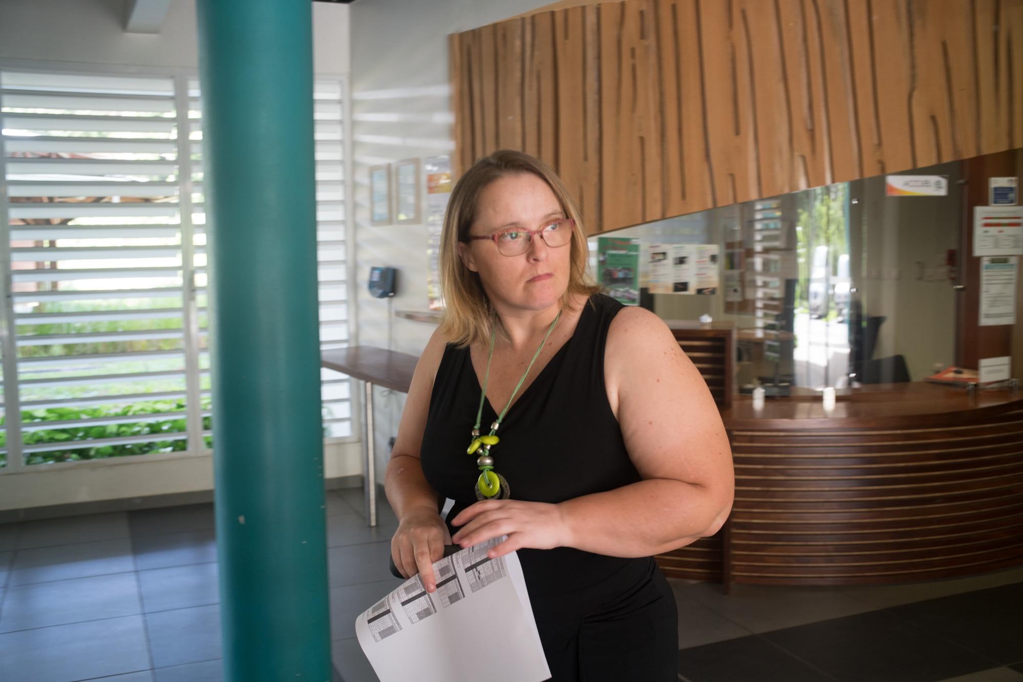 Lucy se tient devant l'accueil, téléphone et document à la main.