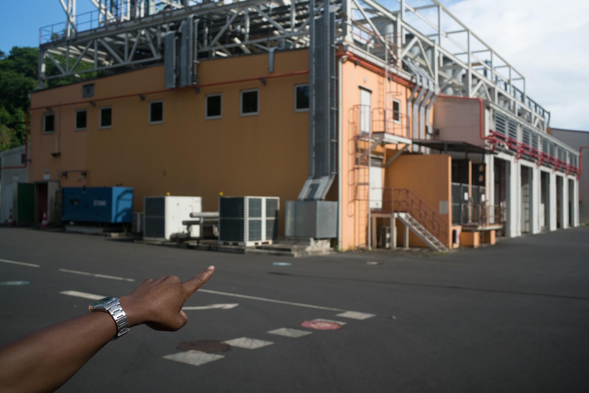 La main de Soihibou désigne un bâtiment surmonté de structures en métal.