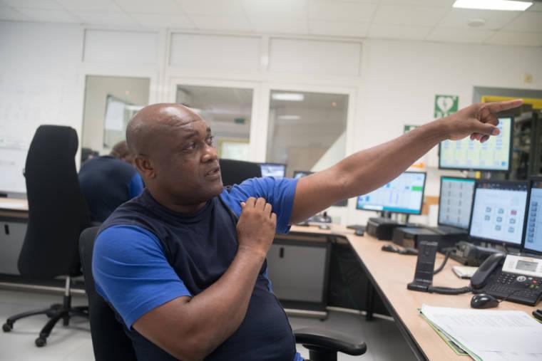 Assis à son bureau, Soihibou pointe quelque chose du doigt.