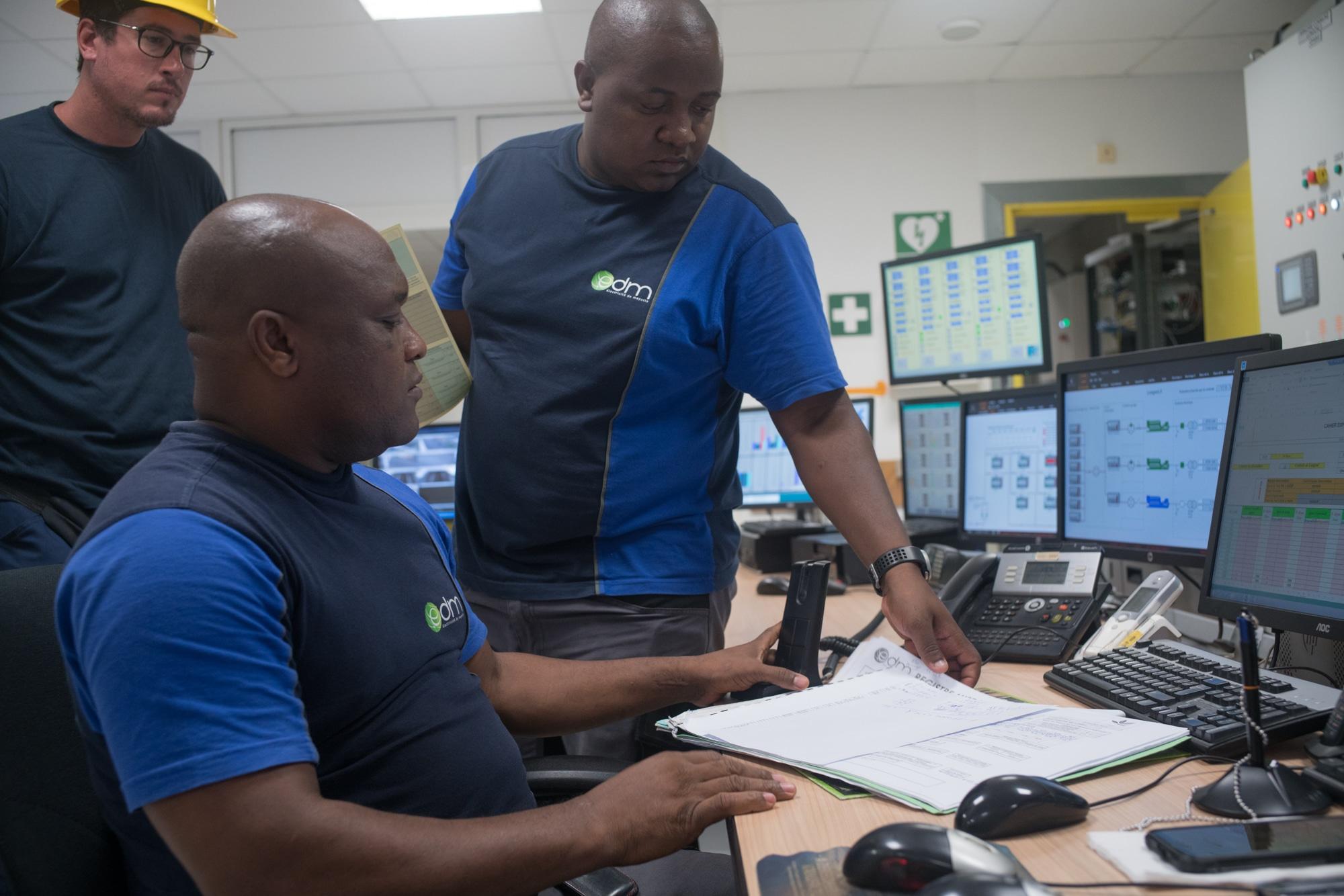 Soihibou travaille à son bureau avec deux collègues.