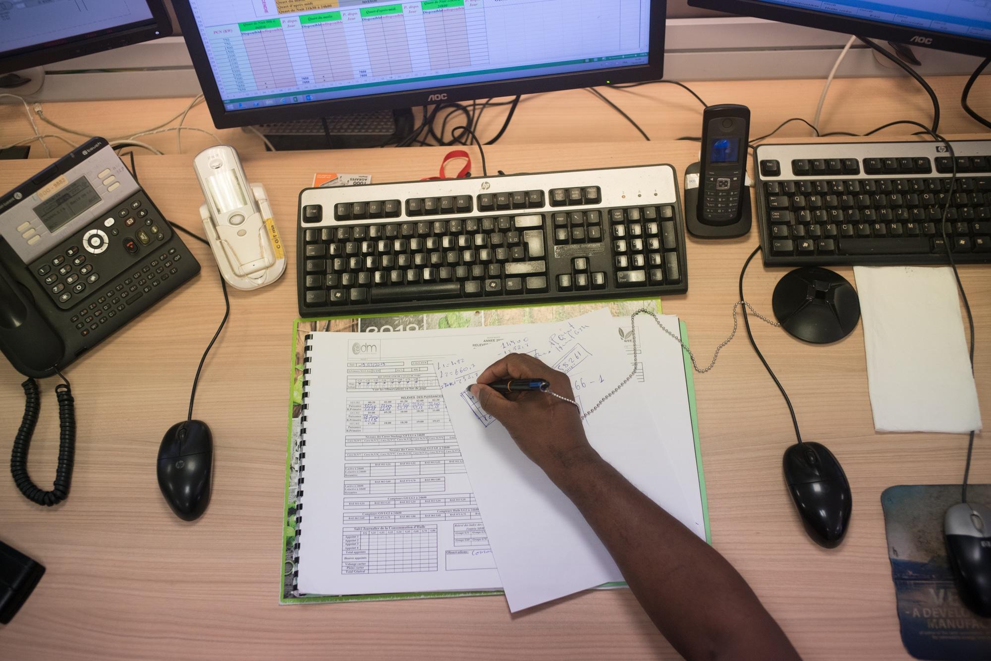 La main de Soihibou, vue de haut, effectue des calculs sur une feuille blanche, sur son bureau.