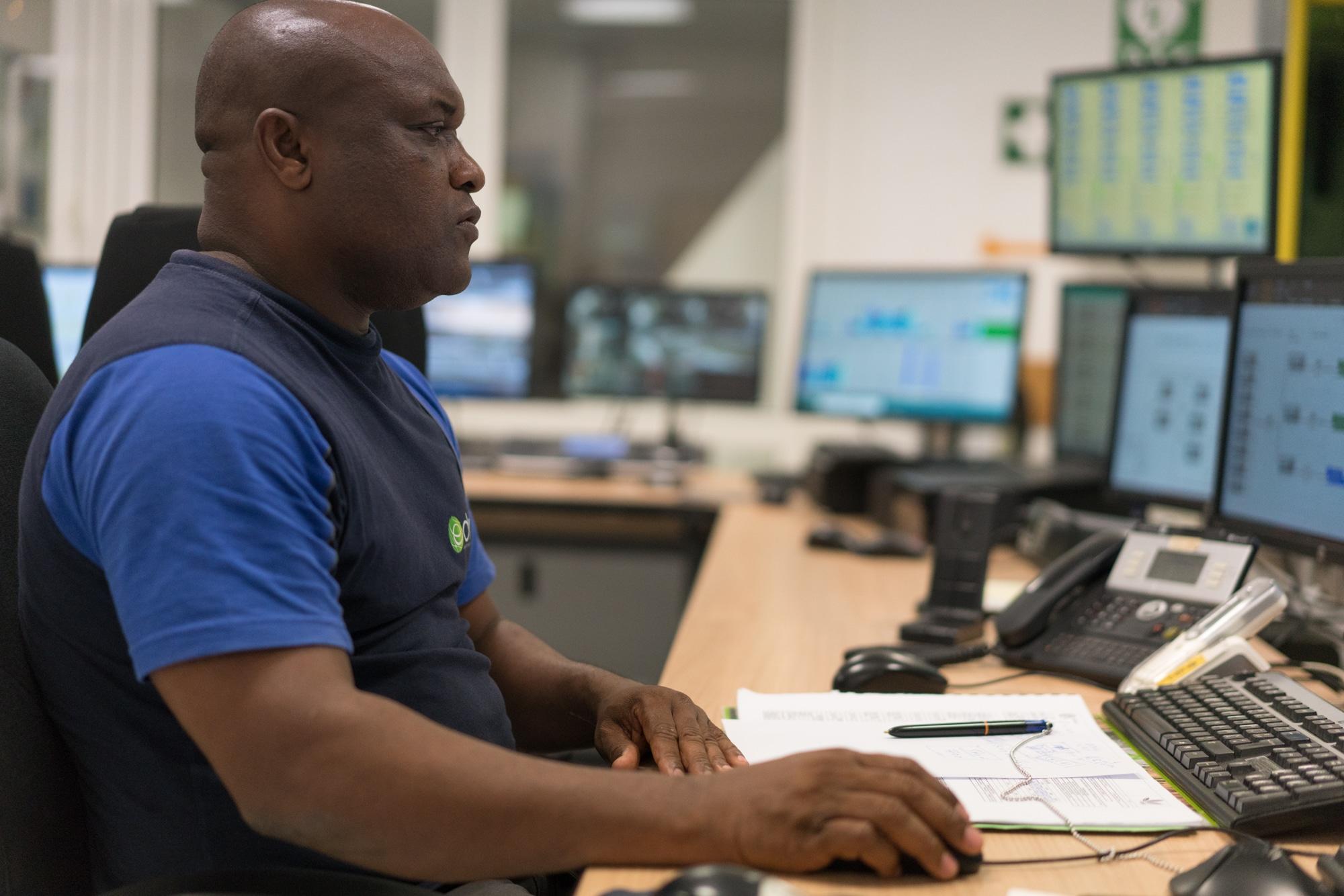 Soihibou, vu de profil droit, travaille sur son ordinateur.
