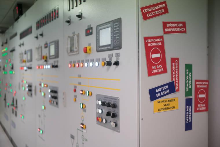 """Le panneau de contrôle, vu de côté. Sur la tranche du panneau, différents signes sont aimantés : """"moteur en essai"""", """"ne pas lancer sans autorisation"""", """"moteur en rodage"""", """"vérification technique""""..."""