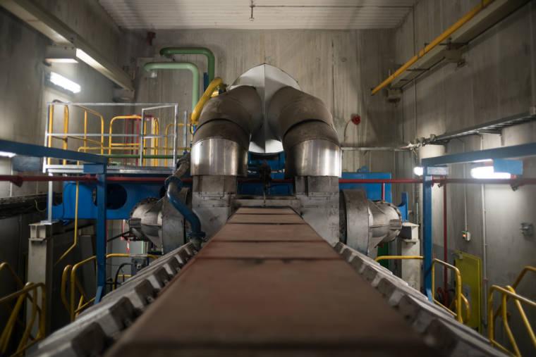 À l'intérieur du bâtiment, des machines de métal côtoient des tuyaux colorés.