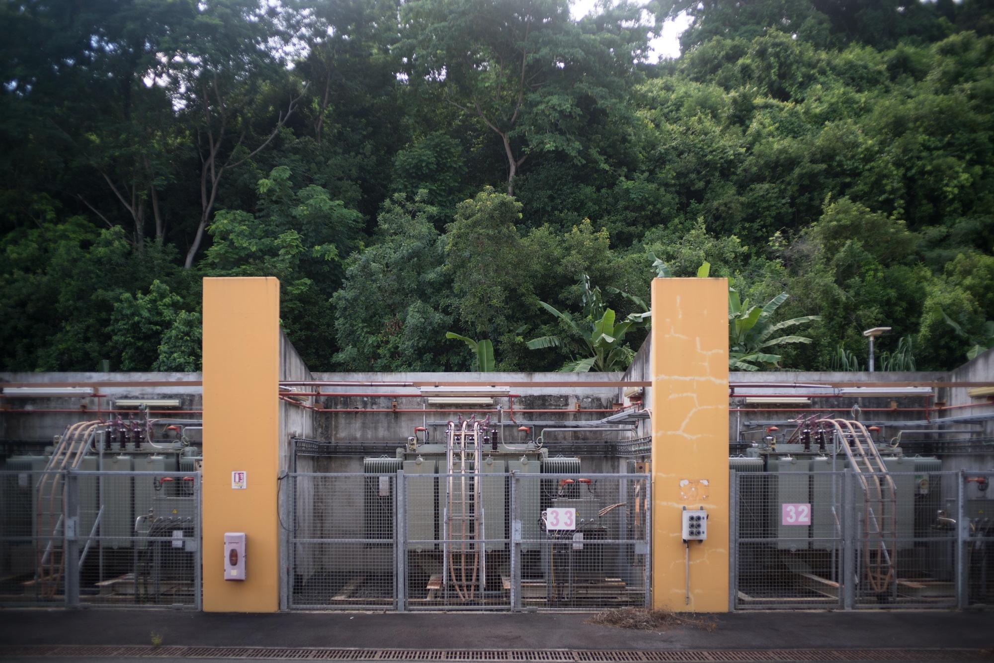 Des installations électriques sont séparées par des murets orange, à l'extérieur. Au fond, une forêt luxuriante.