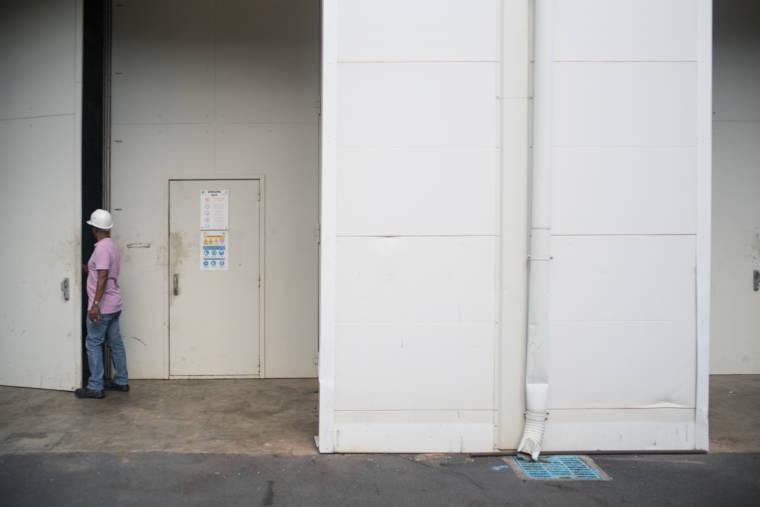 Soihibou emprunte une grande porte pour entrer dans un bâtiment blanc.