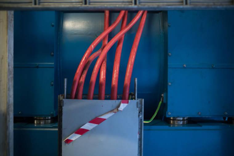 Sur un fond de métal bleu, des tuyaux rouges partent d'un boîtier en métal.