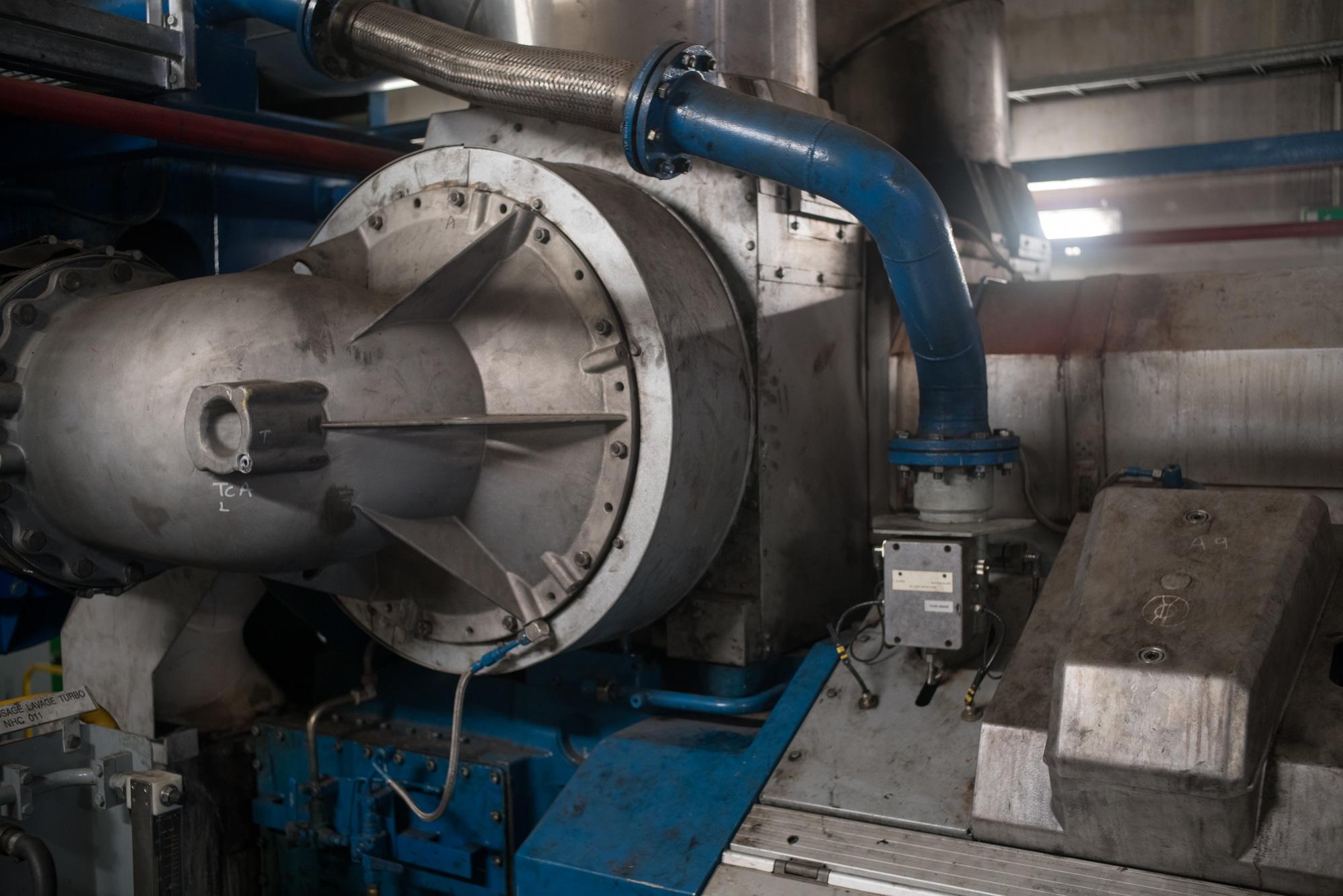 On aperçoit une grosse machine métallique encadrée de tuyaux bleux.
