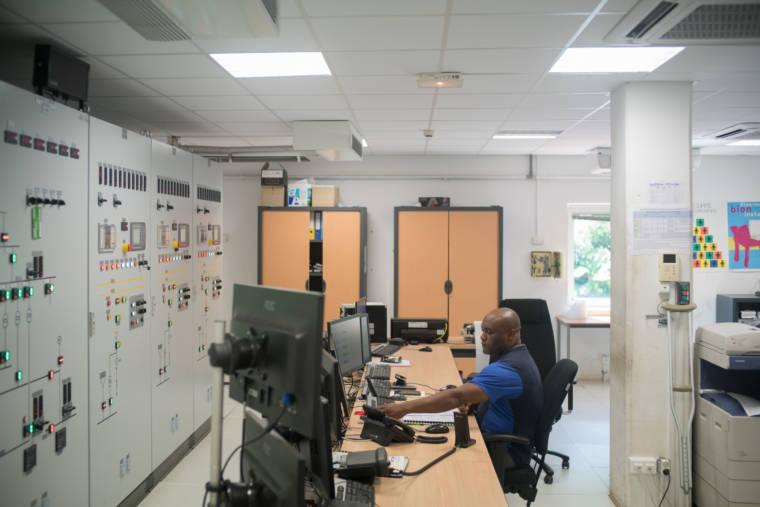 Soihibou Mari est assis à son bureau, devant des panneaux constitués de voyants et de boutons.