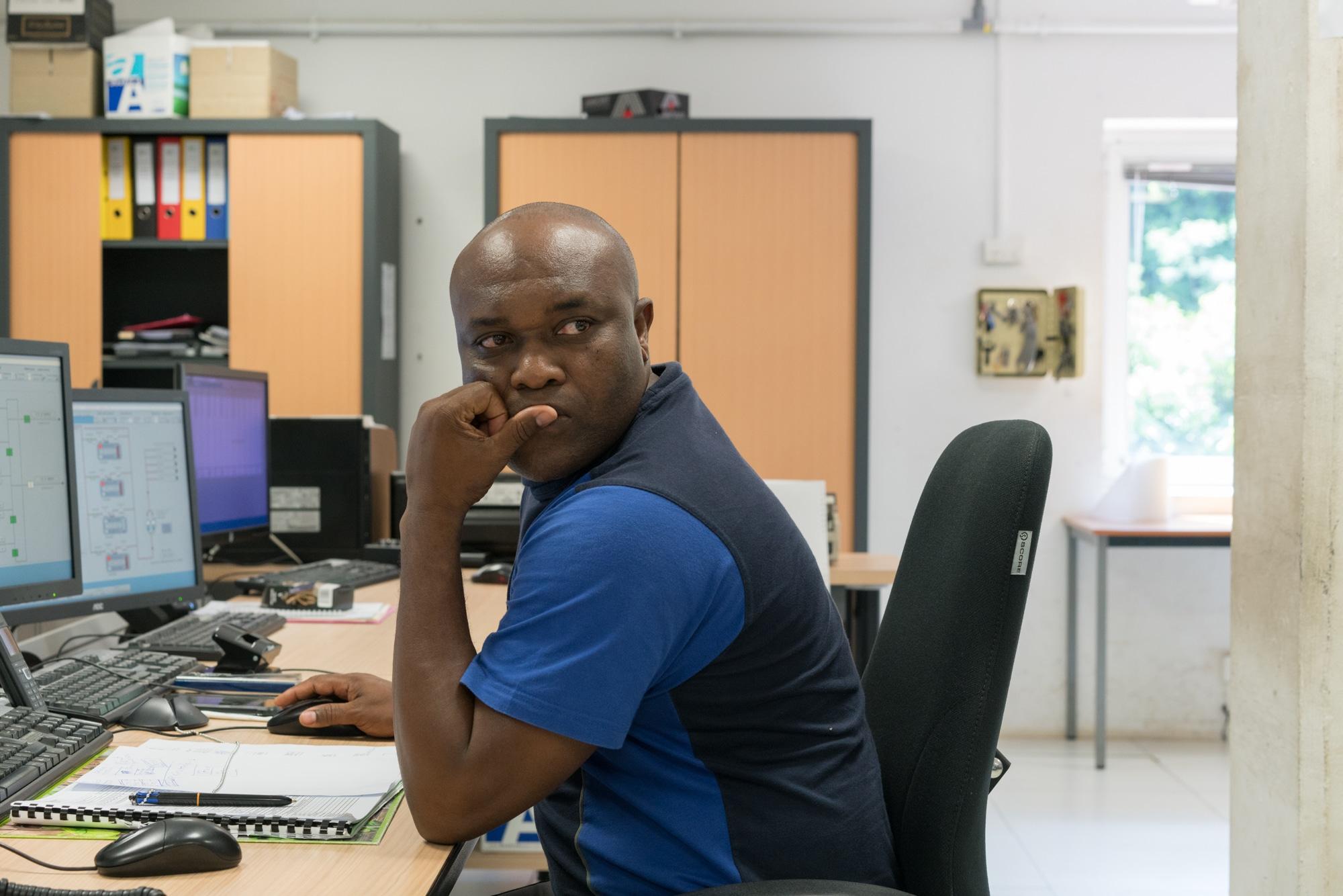 Soihibou, de profil, assis à son bureau, est appuyé sur sa main gauche et regarde vers la gauche.