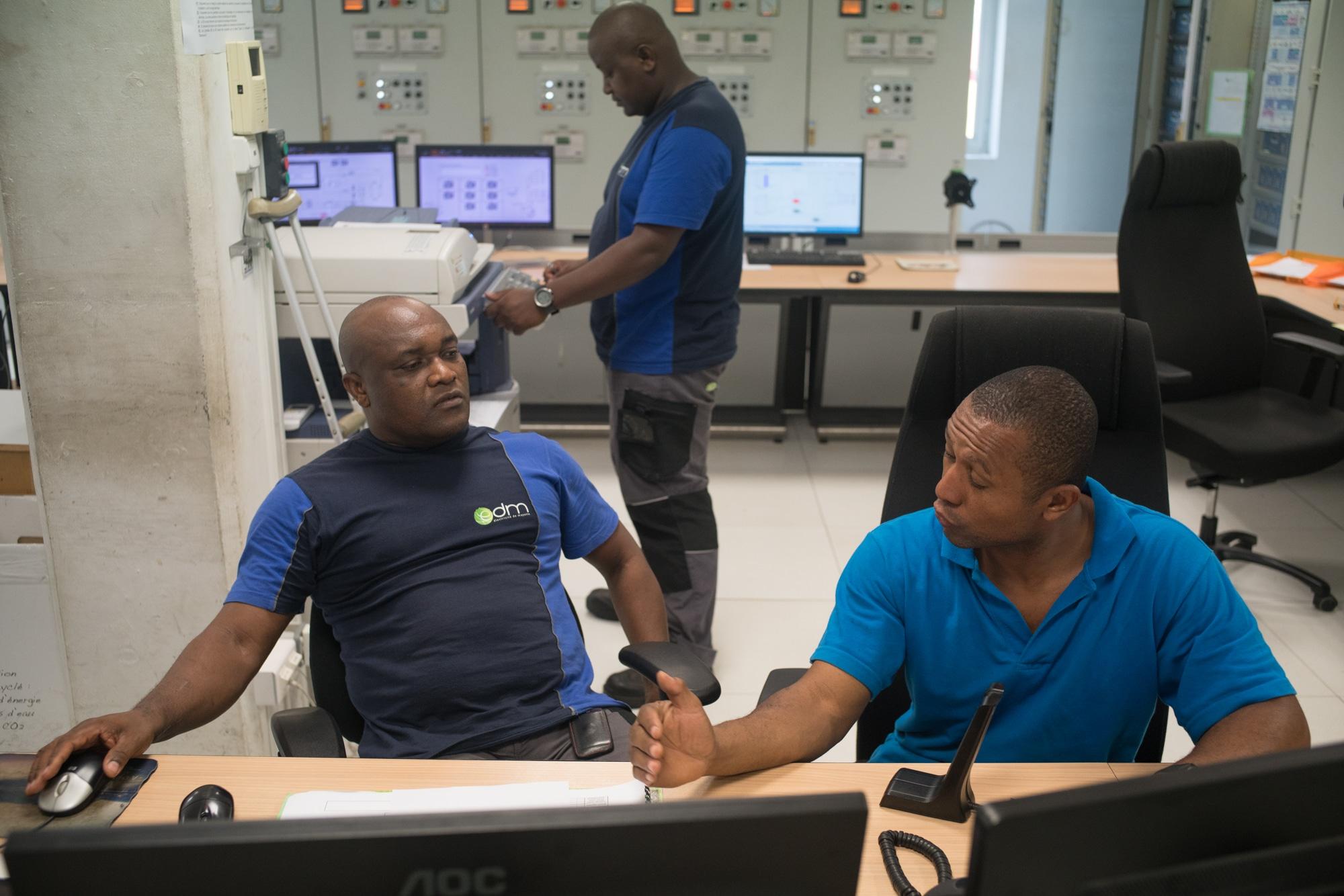 Soihibou, à son bureau, discute avec un collègue. Au deuxième plan une personne fait des photocopies.