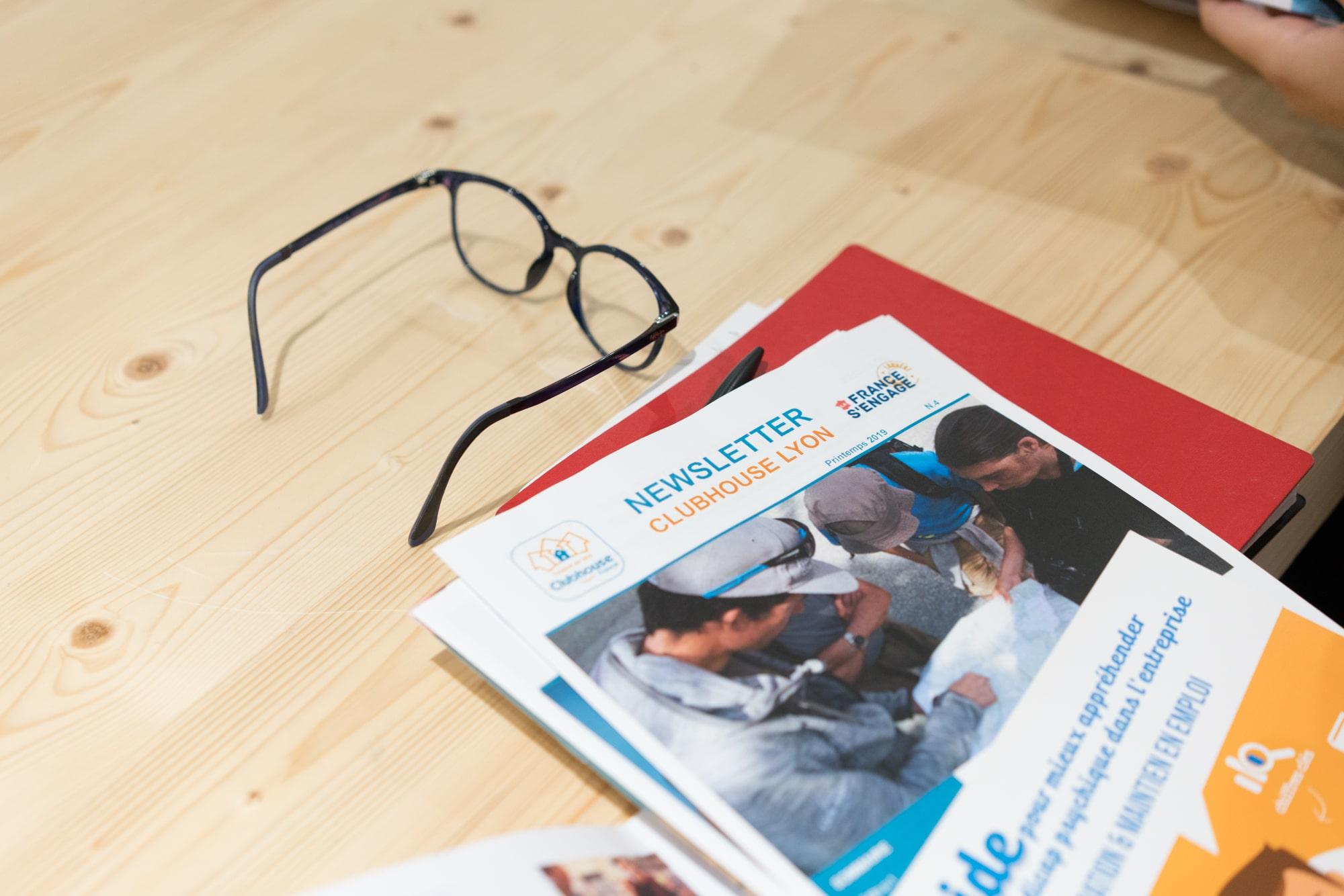 Une paire de lunettes est posée à côté de la newsletter du Clubhouse Lyon, sur une table en bois.