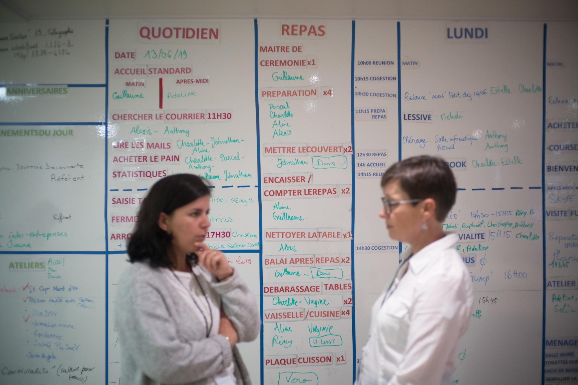 Mathilde discute avec une personnes devant le tableau des tâches.