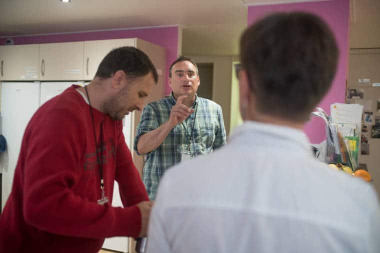 Mathilde, de dos, discute avec un homme au second plan.