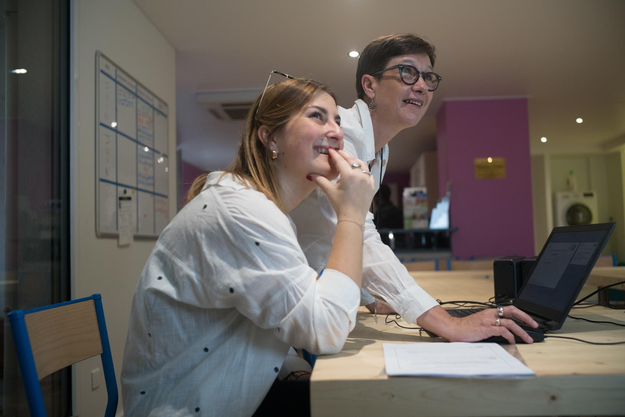 Mathilde projette un fichier à l'aide d'un ordinateur, à côté d'une personne. Toutes deux sourient en regardant l'écran.