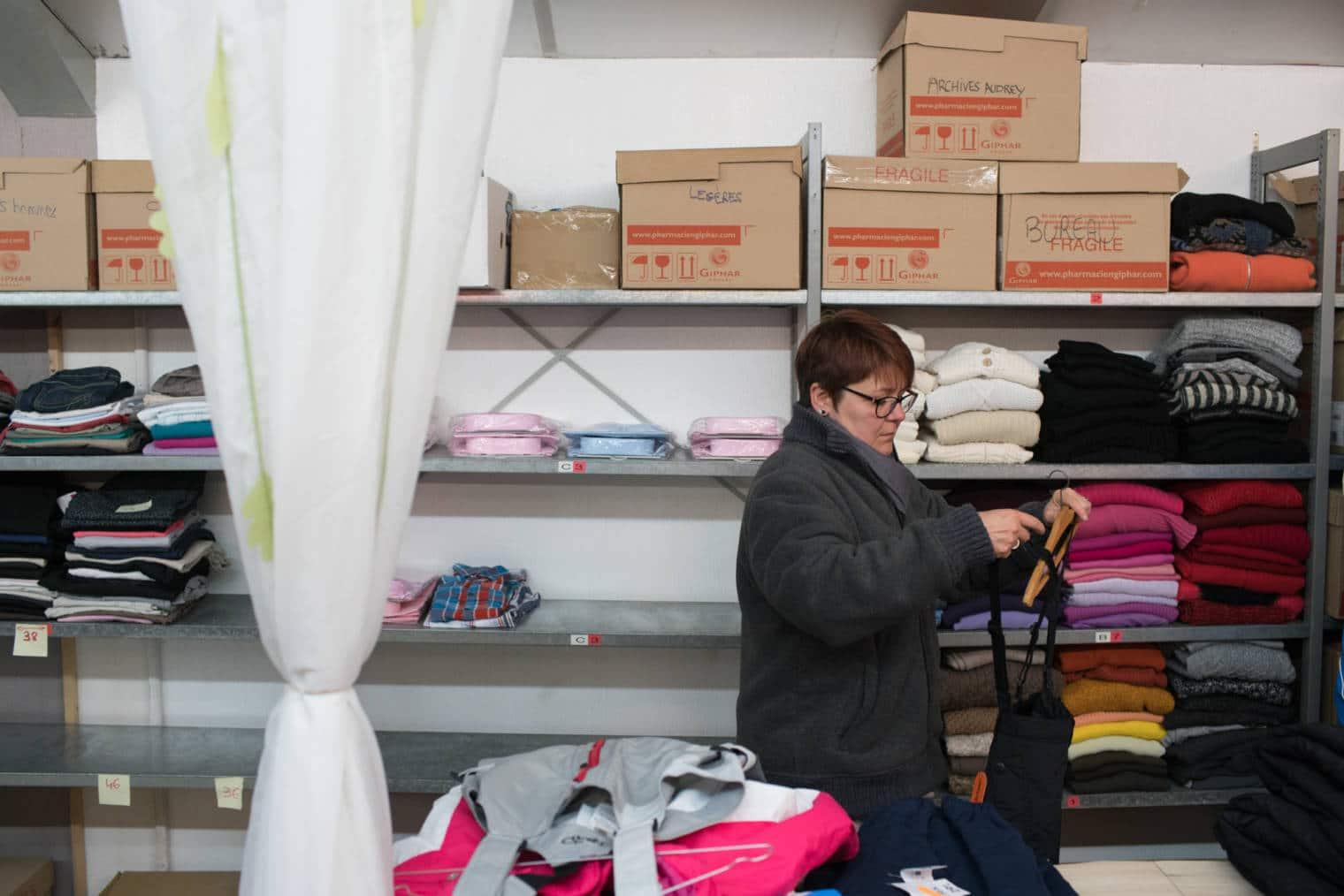 Nathalie pend un vêtement à un ceintre. Elle est entourée d'étagères remplies de vêtements.