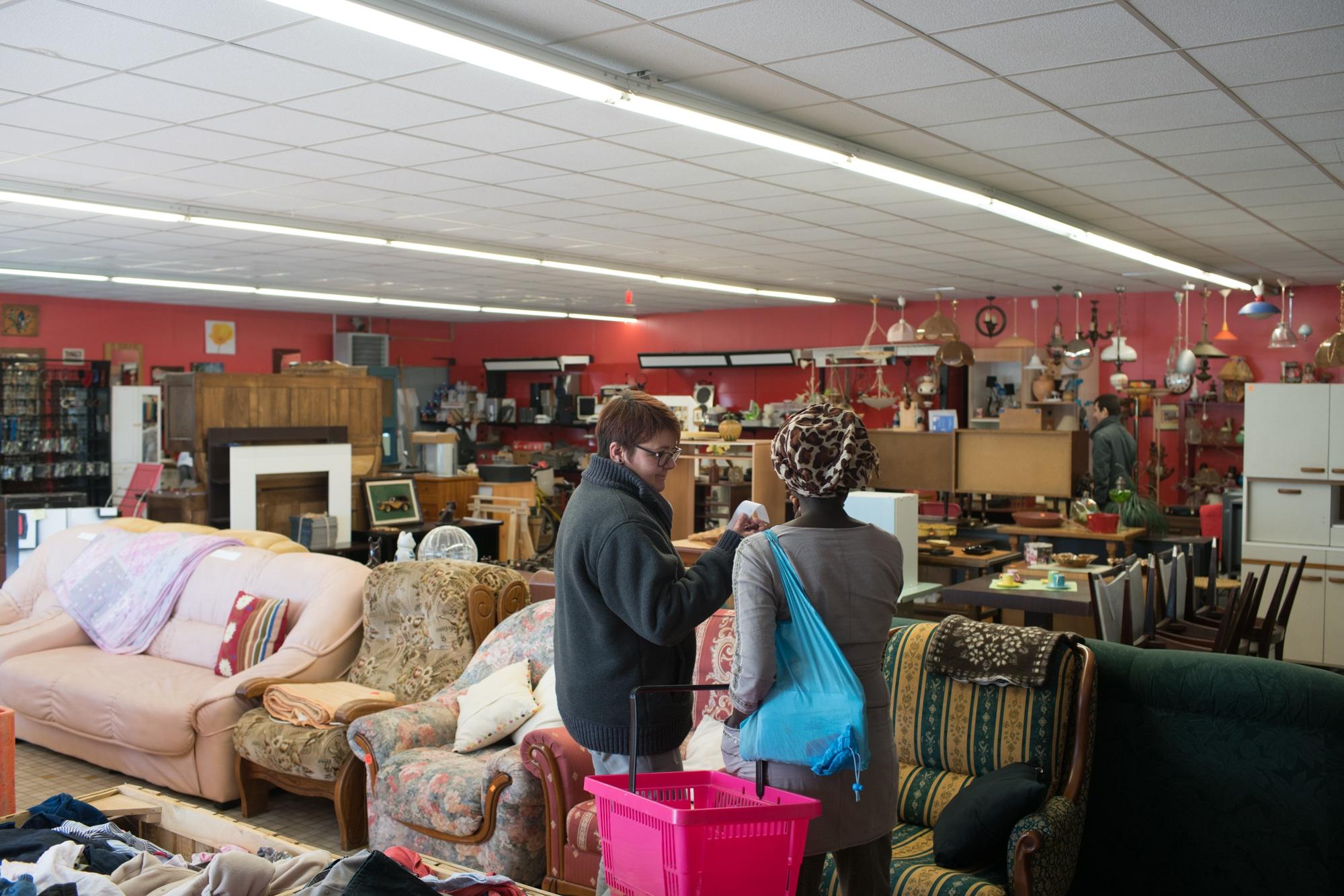 Dans une vaste pièce emplie de meubles et de divers objets, Nathalie échange avec une cliente.